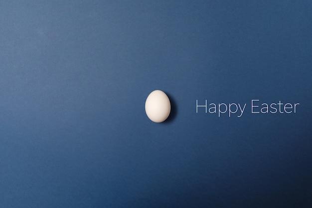 Oeuf de pâques blanc avec mot joyeuses pâques, concept de vacances. fond bleu.