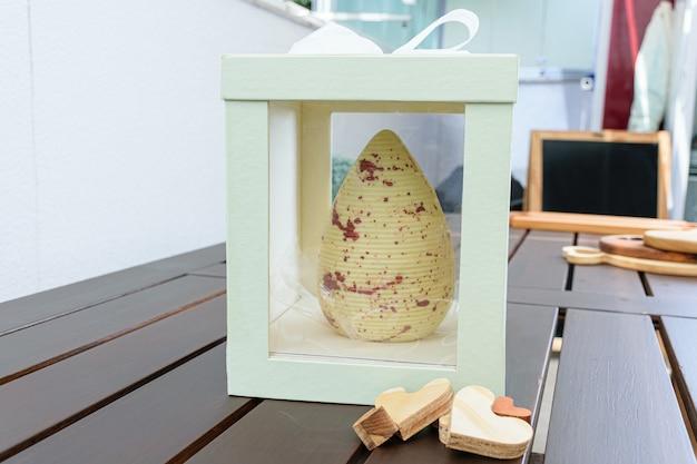 Oeuf de pâques en chocolat blanc avec peinture comestible de couleur cuivre. à l'intérieur d'une boîte blanche avec un ruban d'arc. à côté des coeurs en bois.