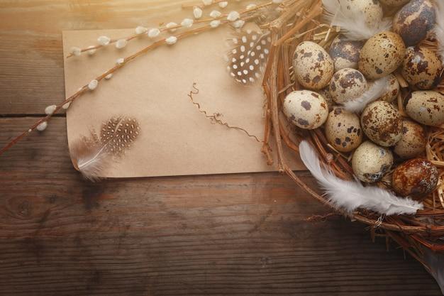 Oeuf de pâques coloré dans le nid sur une planche de bois sombre.