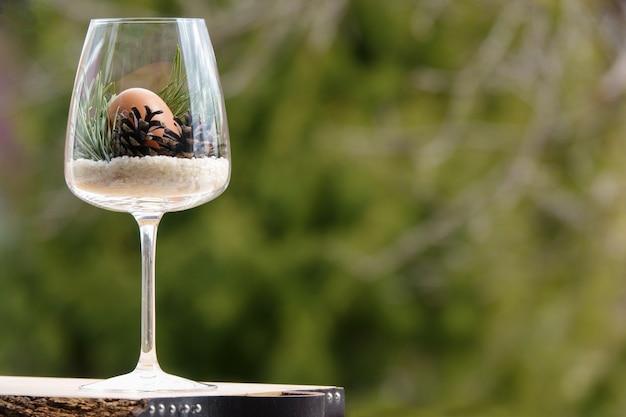 Oeuf de pâques dans un verre décoré avec des cônes naturels et une branche de pin avec fond