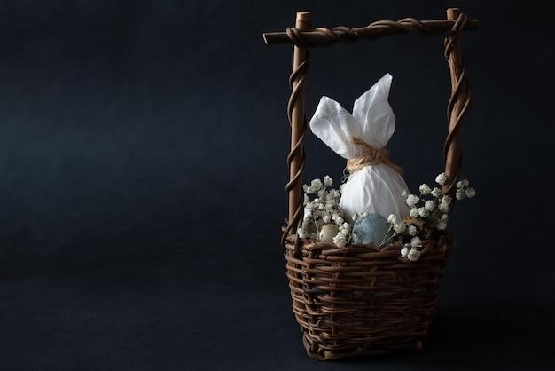 Oeuf de pâques décoré avec des oreilles de lapin dans un panier en osier avec des œufs et des fleurs blanches sur noir.