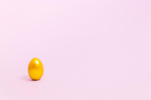 Oeuf de pâques décoré de peinture or sur fond rose. concept pour pâques, printemps. mise au point sélective. copiez l'espace.