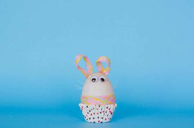 Oeuf de pâques décorer comme lapin sur une tasse en papier cupcake coloré