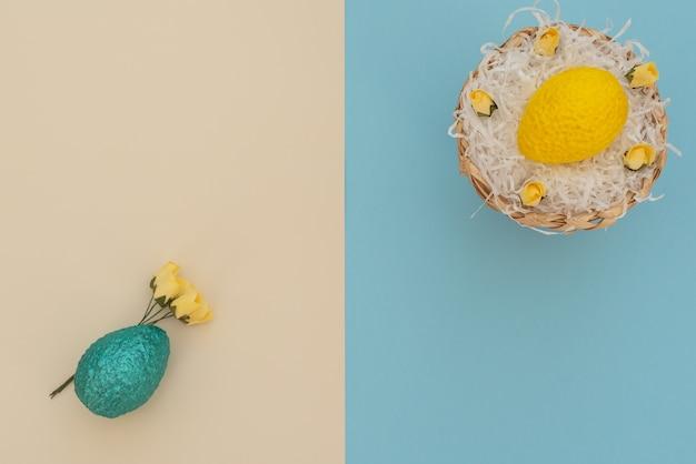 Oeuf de pâques jaune de couleur dans le panier d'oeufs avec du papier blanc comme un nid et oeuf bleu avec des fleurs de printemps jaune