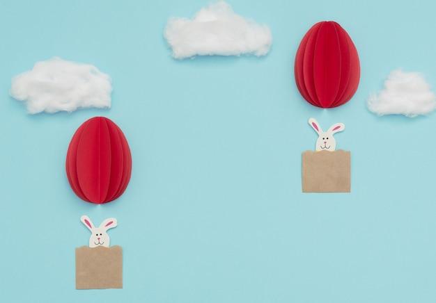Oeuf de pâques montgolfières en papier avec des lapins volent dans le ciel bleu avec des nuages de coton