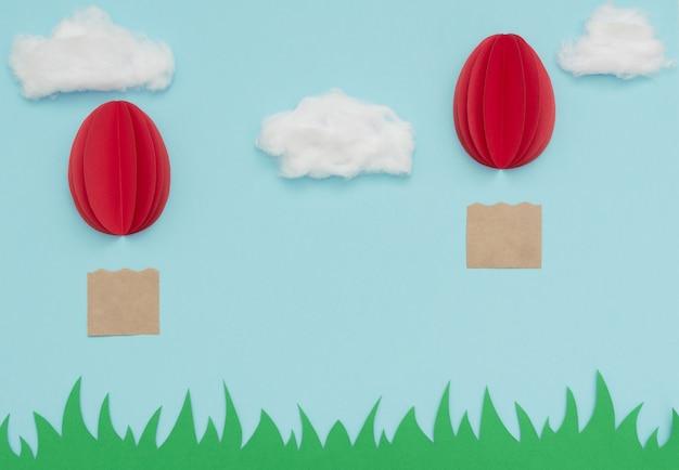Oeuf de pâques montgolfières en papier volent dans le ciel bleu avec des nuages de coton sur l'herbe verte