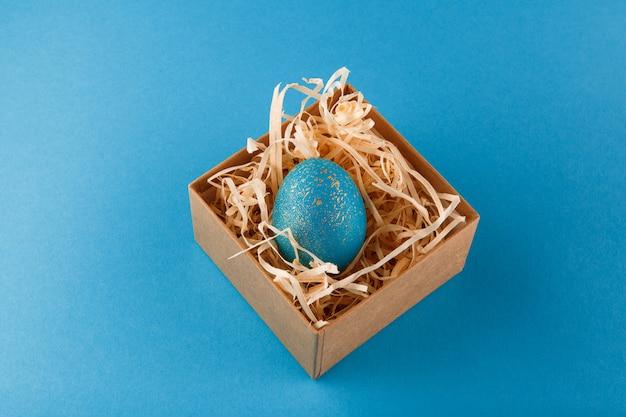 Oeuf de pâques peint en bleu avec de l'or. l'œuf se trouve dans une boîte avec des copeaux de bois. oeuf de pâques peint sur fond bleu. copiez l'espace.