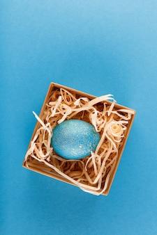 Oeuf de pâques peint en bleu avec de l'or. l'œuf se trouve dans une boîte avec des copeaux de bois. oeuf de pâques peint sur fond bleu. mise à plat. copiez l'espace.