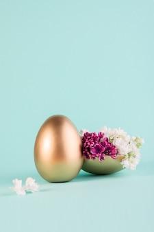 Oeuf de pâques peint en couleur or décoré de fleurs lilas pourpres.