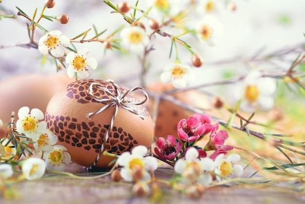 Oeuf de pâques peint sur du bois avec des fleurs blanches et du foin autour