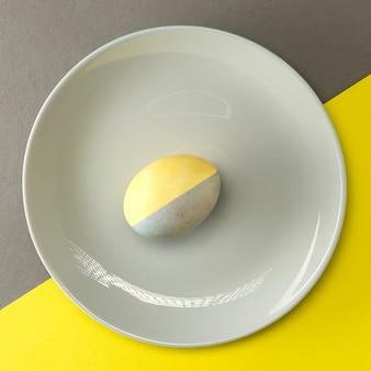 Oeuf de pâques peint en jaune-gris dans une assiette grise sur une surface jaune-gris, orientation carrée