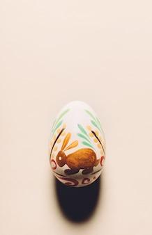 Oeuf de pâques peint à la main portant sur un fond crémeux.