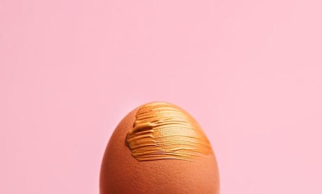 Oeuf de pâques peint avec de la peinture dorée ou surligneur beauté brillant sur fond rose.