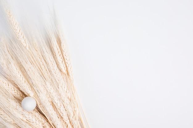 Oeuf de pâques près de bouquet de blé