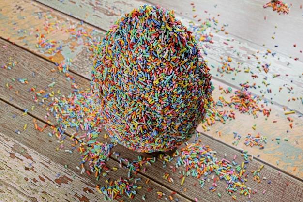 Oeuf de pâques recouvert de pépites de chocolat colorées. sur une table en bois.