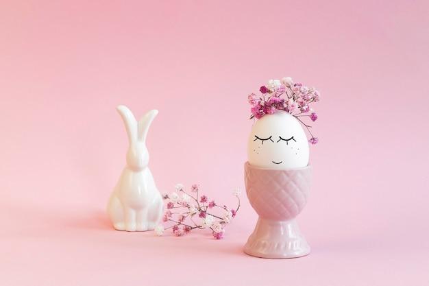 Oeuf de pâques avec un visage dessiné au marqueur noir dans un vase rose avec des fleurs et lapin sur rose.