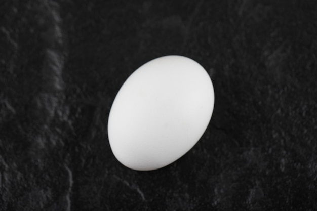 Un œuf de poule blanc frais sur un tableau noir.