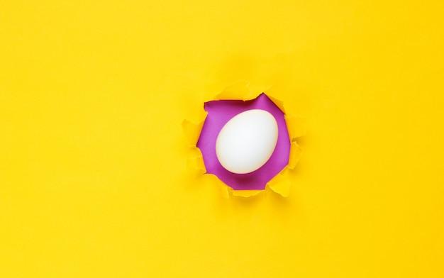 Oeuf de poule blanc à travers le trou déchiré de papier jaune. concept de minimalisme