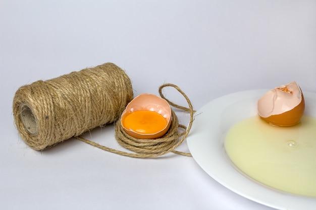 Oeuf de poule cassé en fil décoratif sur blanc