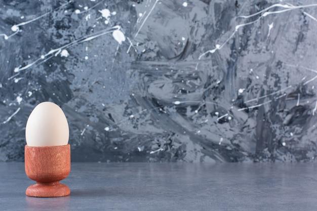 Œuf de poule cru dans un coquetier placé sur une table en pierre.