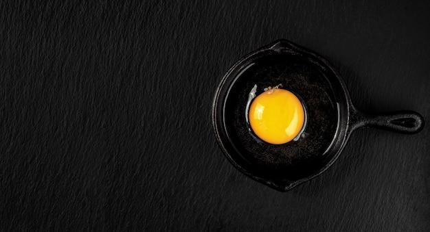 Oeuf de poule cru frais dans une poêle en acier