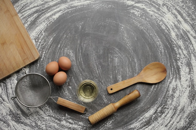 Oeuf de poule, farine, huile d'olive, ustensile de cuisine sur fond de tableau gris.