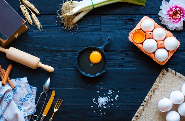 Œuf de poulet avec des ustensiles de cuisine sur une table en bois