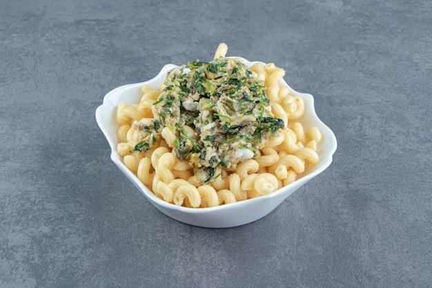 Oeuf savoureux avec des verts et des pâtes dans un bol blanc.