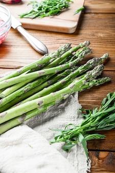 Oeufs d'asperges biologiques et ingrédients de vinaigrette française avec moutarde de dijon, oignon haché au vinaigre rouge taragon sur fond vieux en bois clair, vue latérale verticale.