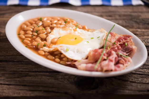 Oeufs au plat avec bacon bio, pommes de terre rissolées et toasts croustillants