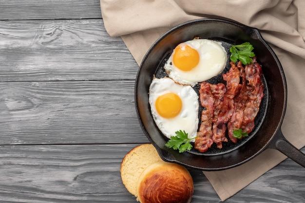 Oeufs au plat avec bacon dans une casserole. vue de dessus.