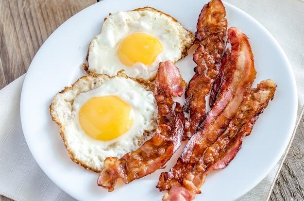 Oeufs au plat avec bacon sur la table en bois