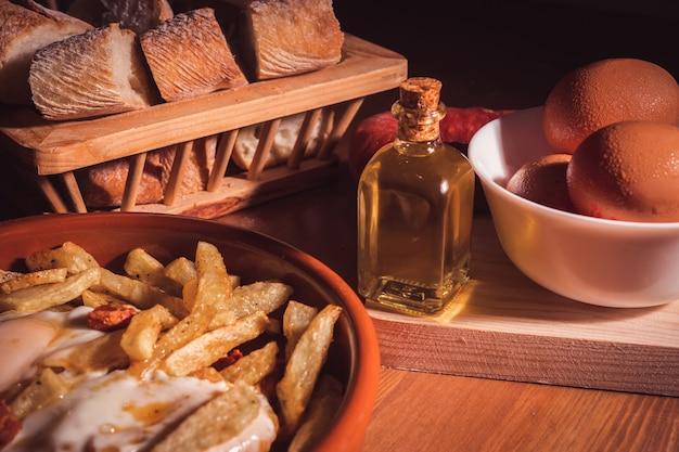 Oeufs au plat, frites, huile d'olive et pain sur une table en bois