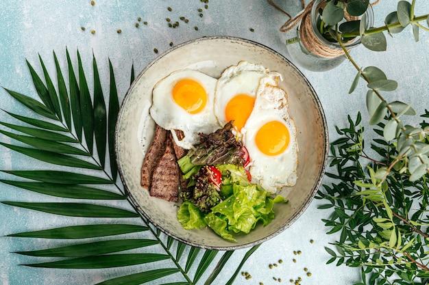Œufs au plat gastronomiques avec rôti de bœuf et salade