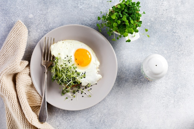 Oeufs au plat avec microgreen de roquette dans une plaque en céramique grise sur fond ancien en béton gris. petit déjeuner anglais traditionnel. vue de dessus