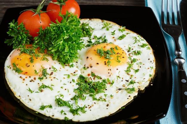 Oeufs au plat sur un plat noir servi avec du persil et des tomates