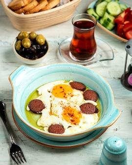 Oeufs au plat avec saucisse et bol aux olives