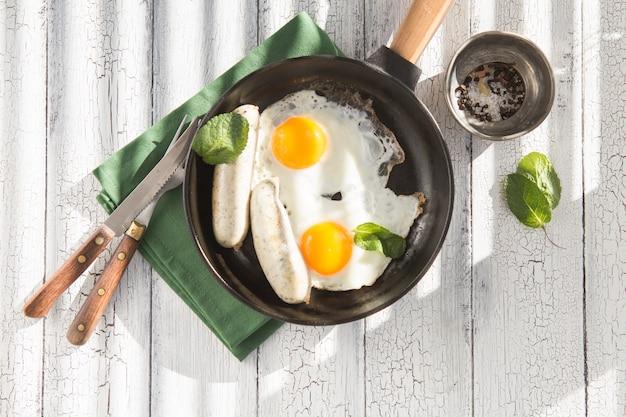 Oeufs au plat, saucisse dans une poêle en fer - petit-déjeuner anglais de nourriture saine. bloc de couleur