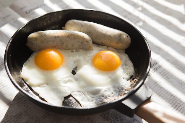 Oeufs au plat, saucisse dans une poêle en fer - petit-déjeuner anglais