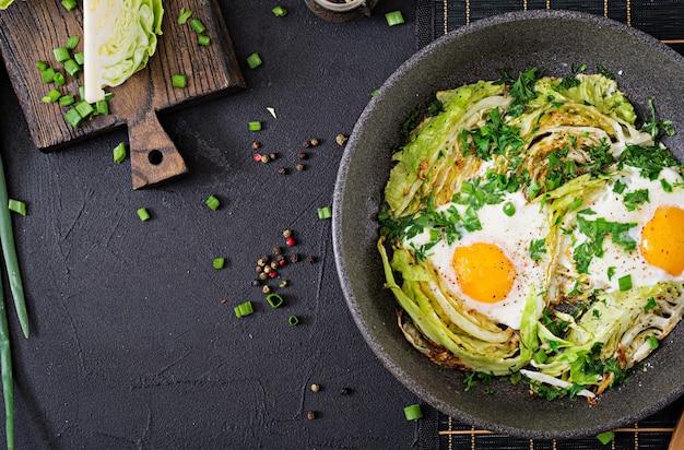 Oeufs au plat avec des tranches de jeune chou et verts. petit déjeuner nutritif. vue de dessus. mise à plat
