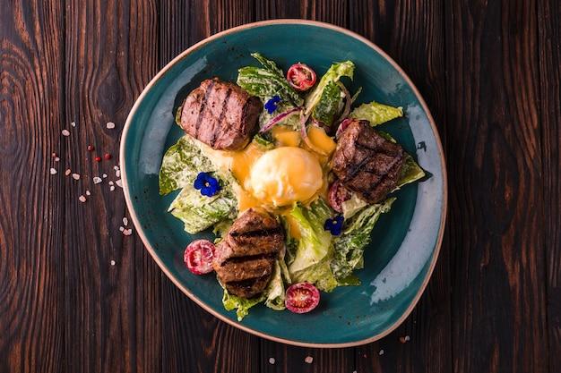 Œufs bénédictine à la viande de bœuf sur une grande assiette blanche