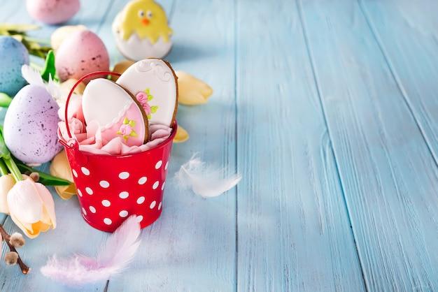 Œufs de biscuits de pain d'épice de joyeuses pâques avec seau et tulipes avec des œufs colorés