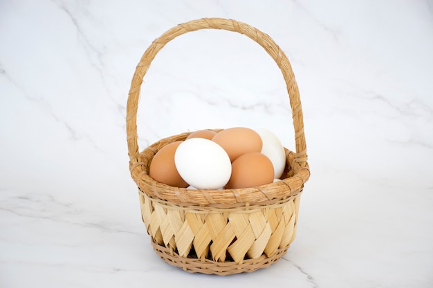 Oeufs blancs et bruns dans un panier en osier sur fond de marbre. œufs de poule frais de la ferme. joyeuses pâques.