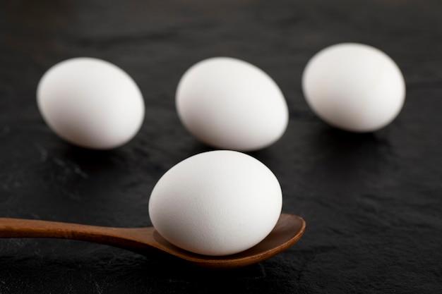 Oeufs blancs crus et cuillère en bois sur une surface noire.