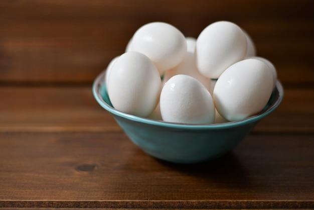 Oeufs blancs dans une assiette en bois sur fond en bois