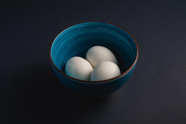 Oeufs blancs dans un bol bleu sur fond sombre plaine noir de mauvaise humeur, vue d'angle, joyeuses pâques