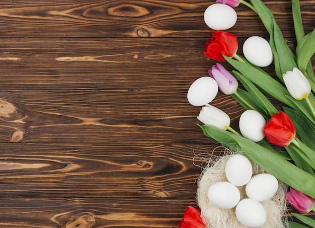 Oeufs blancs dans le nid avec des tulipes sur la table