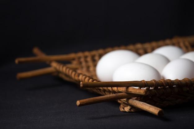 Oeufs blancs dans le panier en osier