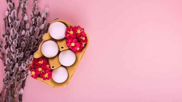 Œufs blancs dans un présentoir avec des fleurs et des branches de saule