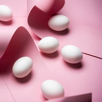 Oeufs blancs sur fond rose